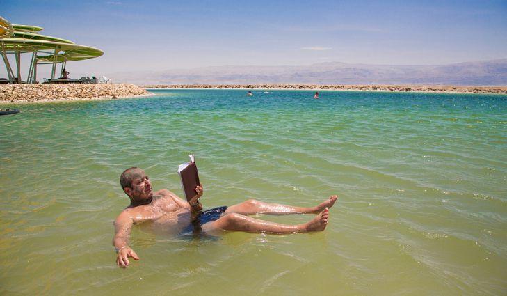 Мужчина, плавающий в Мертвом море и читающий книгу.